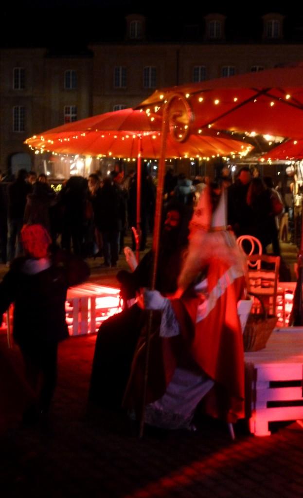 Un enfant va vers saint Nicolas et Père Fouettard un soir sur le marché de Noël