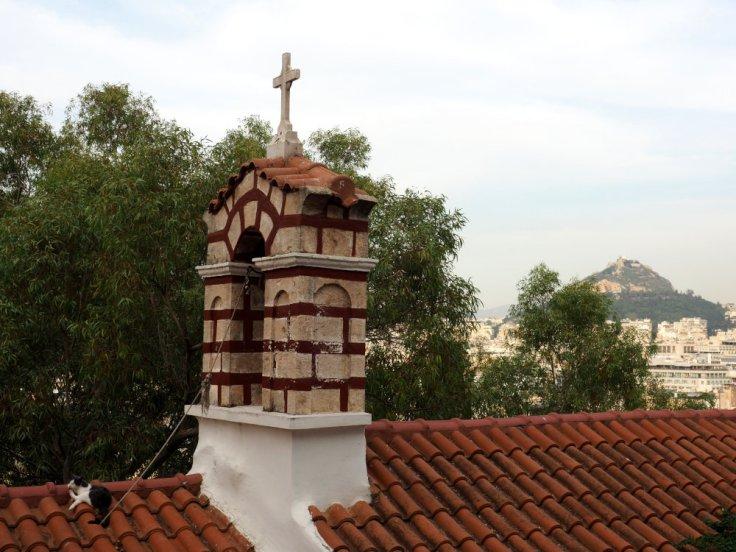 Chat faisant tranquillement sa toilette sur un toit d'une chapelle à Athènes.