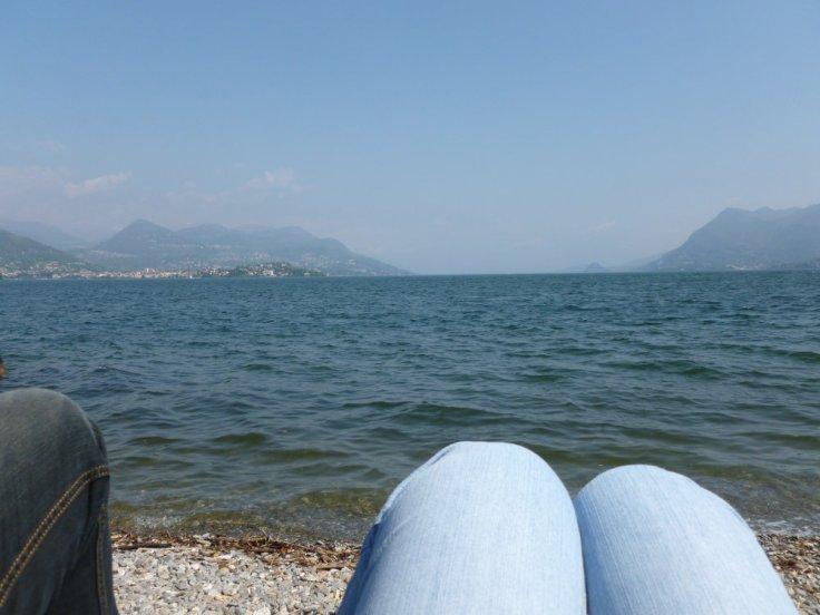 Vue sur le lac Majeur depuis sa rive, genoux au premiers plan