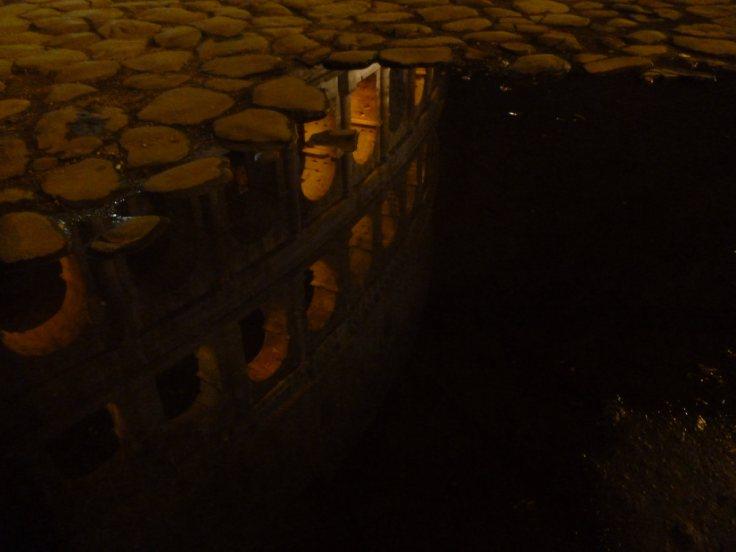 Reflet du Colisée dans une flaque d'eau au milieu des pavés, de nuit.