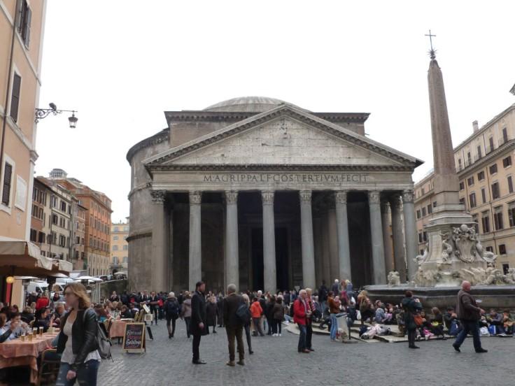Le Panthéon de Rome vu de face avec de nombreux touristes tout petits par rapport au bâtiment.