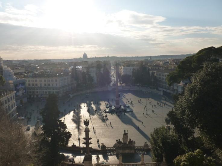 Vue éblouissante et plongeante sur la piazza del Popolo, Rome. Au loin la silhouette de la basilique Saint-Pierre émerge de l'horizon.